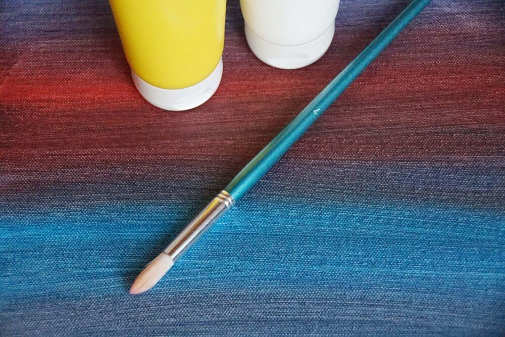 Bemalte Leinwand mit Acrylfarbe in Tuben und Pinsel